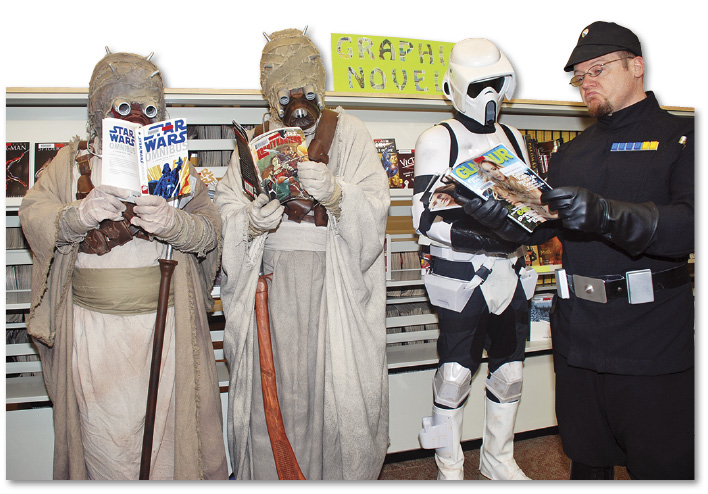 Photo of four people dressed as Star Wars characters reading.